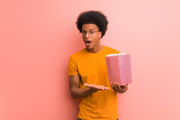 Young african american holding a popcorn bucket holding something on palm hand