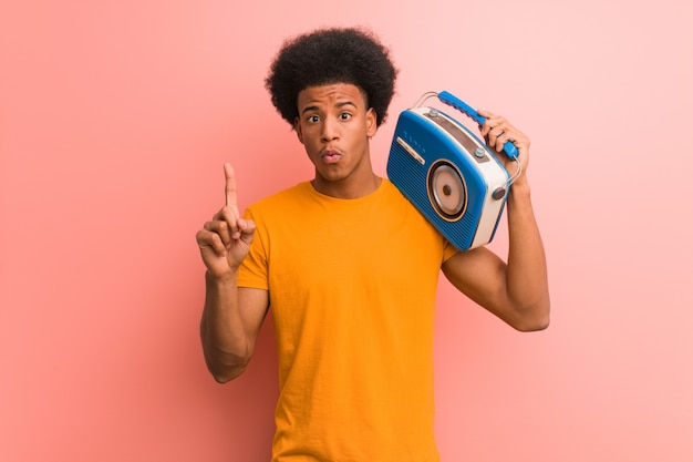 Young african american holding a vintage radio having a great idea, concept of creativity