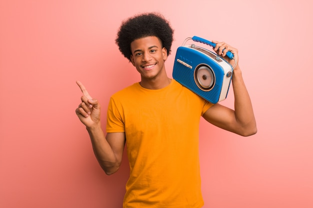 Young african american holding a vintage radio pointing to the side with finger