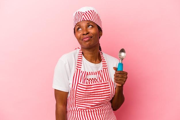 目標と目的を達成することを夢見てピンクの背景に分離されたスクープを保持している若いアフリカ系アメリカ人のアイスクリームメーカーの女性