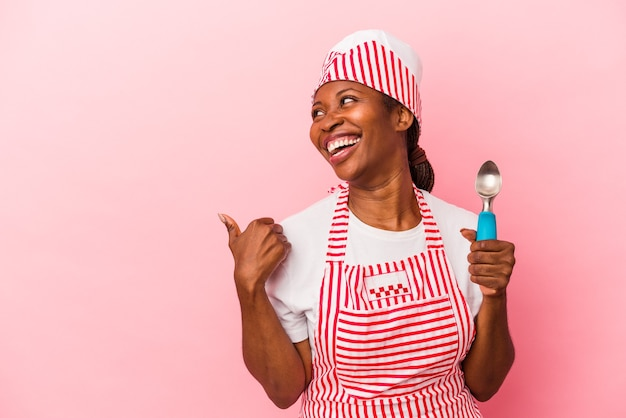 若いアフリカ系アメリカ人のアイスクリームメーカーの女性は、ピンクの背景に分離されたスクープを親指の指で離れて、笑ってのんきなポイントで保持しています。