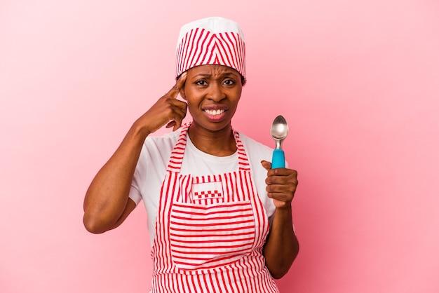 人差し指で失望のジェスチャーを示すピンクの背景に分離されたスクープを保持している若いアフリカ系アメリカ人のアイスクリームメーカーの女性。