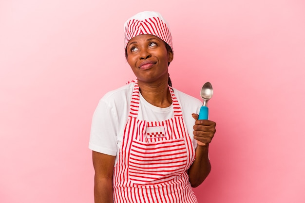 Young african american ice cream maker woman holding scoop isolated on pink background dreaming of achieving goals and purposes