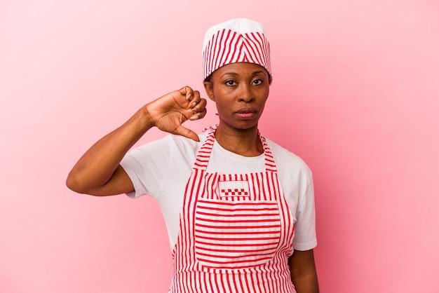 嫌いなジェスチャーを示すピンクの背景に分離された若いアフリカ系アメリカ人のアイスクリームメーカーの女性、親指を下に。不一致の概念。