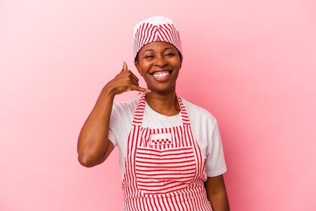 指で携帯電話の呼び出しジェスチャーを示すピンクの背景に分離された若いアフリカ系アメリカ人のアイスクリームメーカーの女性。
