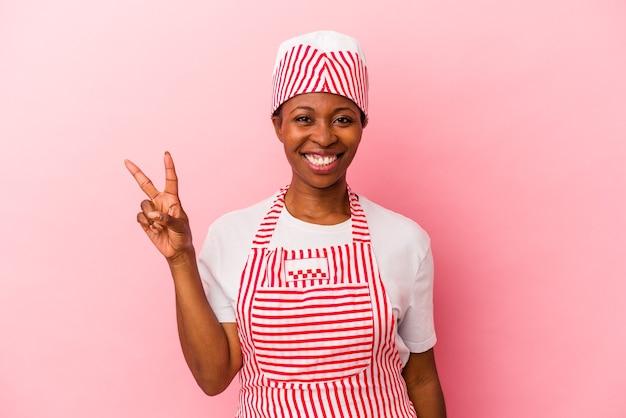 若いアフリカ系アメリカ人のアイスクリームメーカーの女性は、指で2番目を示すピンクの背景に分離されました。
