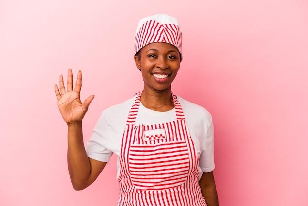 ピンクの背景に分離された若いアフリカ系アメリカ人のアイスクリームメーカーの女性は、指で5番目を示す陽気な笑顔を浮かべています。