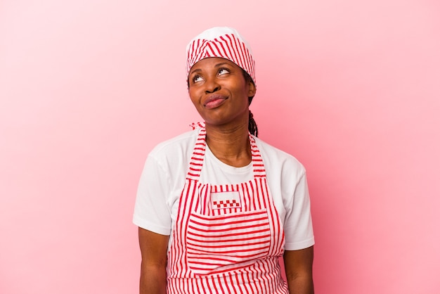 Young african american ice cream maker woman isolated on pink background dreaming of achieving goals and purposes