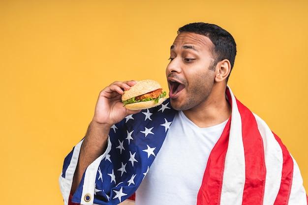 미국 국기와 함께 노란색 배경 위에 고립 된 햄버거를 먹는 젊은 아프리카 계 미국인 인도 흑인 남자. 다이어트 개념입니다.