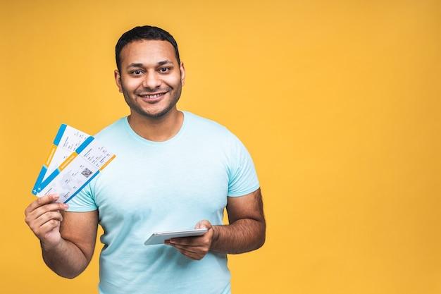 노란색 배경 위에 격리된 탑승권을 들고 있는 젊은 아프리카계 미국인 인도 흑인 남자. 태블릿 컴퓨터를 사용합니다.