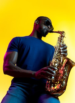 Young african-american jazz musician playing the saxophone on yellow studio background in trendy neon light. concept of music, hobby. joyful  guy improvising. colorful portrait of artist.