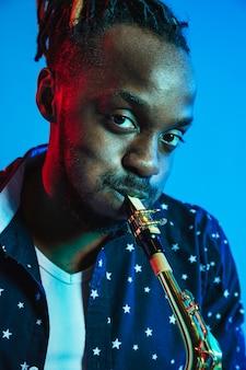 파랑에 색소폰을 연주하는 젊은 아프리카 계 미국인 재즈 음악가
