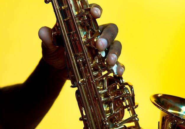 トレンディなネオンの光の中で黄色の背景にサックスを演奏する若いアフリカ系アメリカ人のジャズミュージシャン。