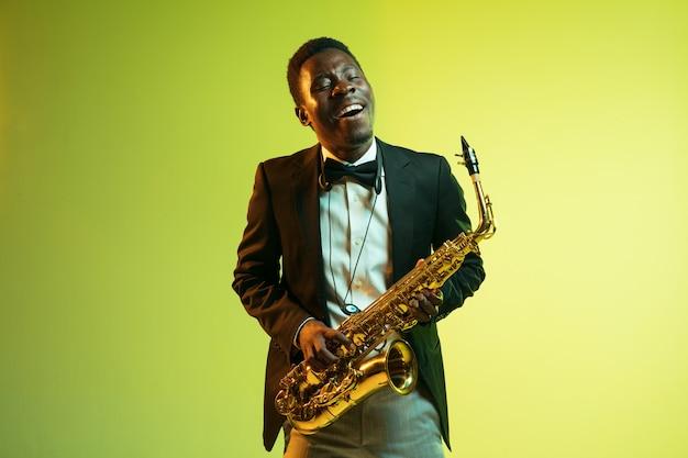サックスを演奏する若いアフリカ系アメリカ人のジャズミュージシャン