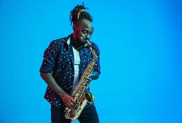 Молодой афро-американский джазовый музыкант играет на саксофоне