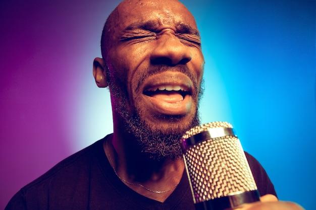 Молодой афро-американский джазовый музыкант поет песню на градиентном фиолетово-синем