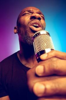 紫青のグラデーションで歌を歌う若いアフリカ系アメリカ人のジャズミュージシャン