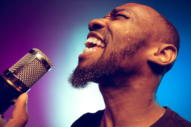 Young african-american jazz musician singing a song on gradient purple-blue