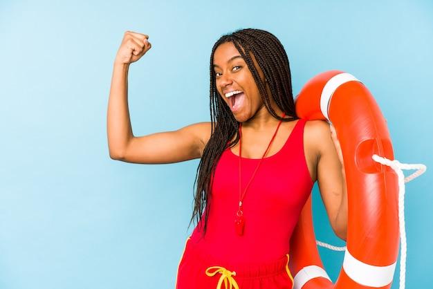 若いアフリカ系アメリカ人のライフガードの女性は勝利、勝者の概念の後、拳を上げて分離しました。