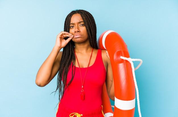 Молодая афро-американская женщина-охранник жизни изолирована с пальцами на губах, хранящих в секрете.