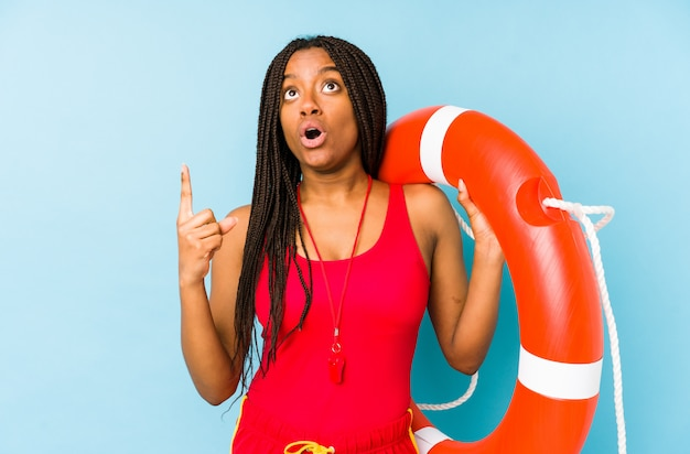열린 입으로 거꾸로 가리키는 젊은 아프리카 계 미국인 생명 가드 여자.