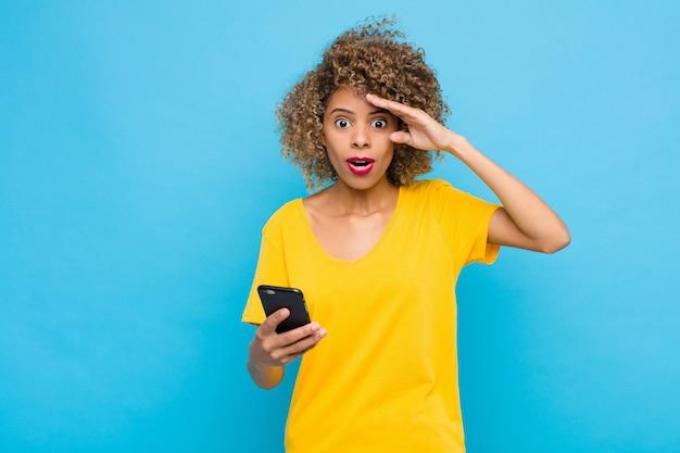 Молодой афроамериканец выглядит счастливым, удивленным и удивленным, улыбающимся и понимающим удивительные и невероятно хорошие новости с помощью мобильного телефона