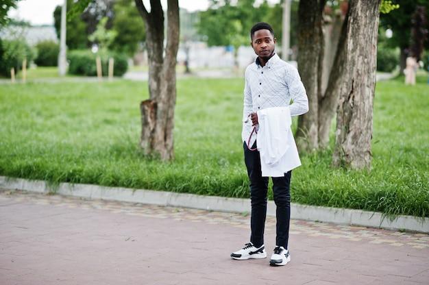 若いアフリカ系アメリカ人の男性医師は、屋外で提起された聴診器で手に白いコートを保持します。