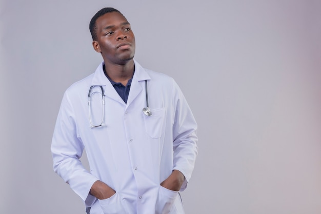 Young african american male doctor wearing white coat with stethoscope with hands in pockets looking aside with confident serious expression on face
