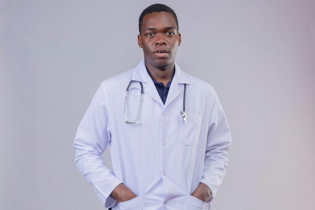 Young african american male doctor wearing white coat with stethoscope with hands in pockets  with serious confident expression