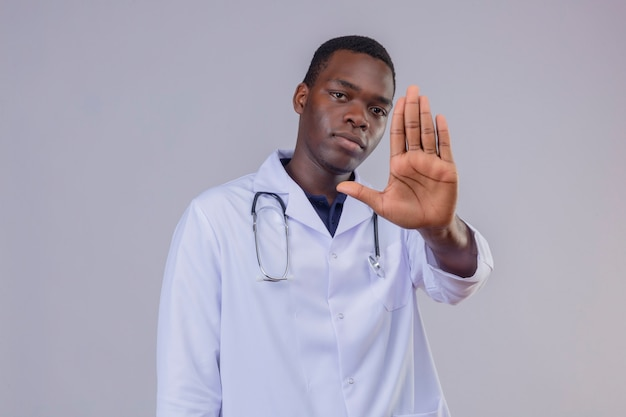 Young african american male doctor wearing white coat with stethoscope  with serious face with open hand making stop sign