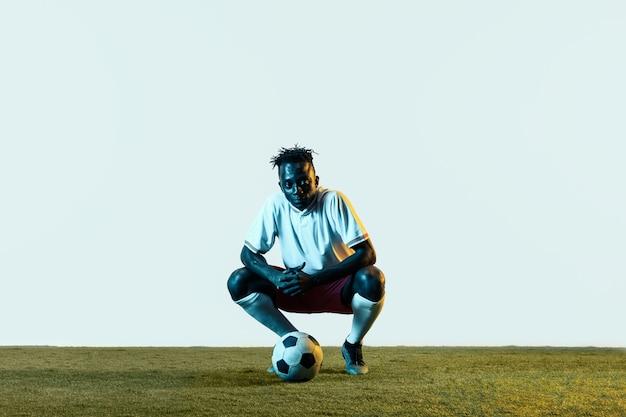 Молодой афро-американский футболист или футболист в спортивной одежде и ботинках сидит с мячом в неоновом свете, изолированном на белом фоне. концепция здорового образа жизни, профессионального спорта, хобби.