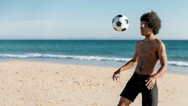 Young african american male playing soccer on seashore