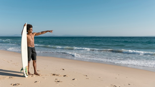 Young african american male pointing at ocean