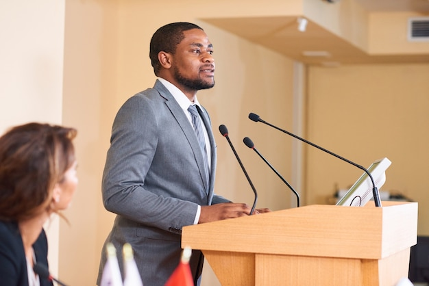 Young african-american male speaker talking in microphone while making speech by tribune for business colleagues or delegates