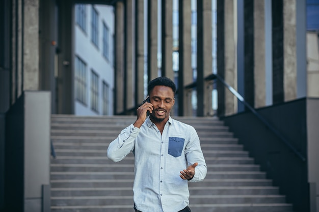 Young african american male student having fun talking on cell phone
