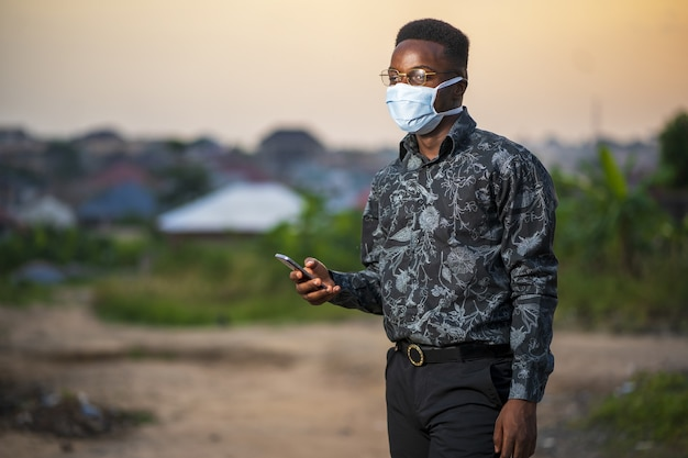 Young african american male wearing a protective face mask using his phone outdoors