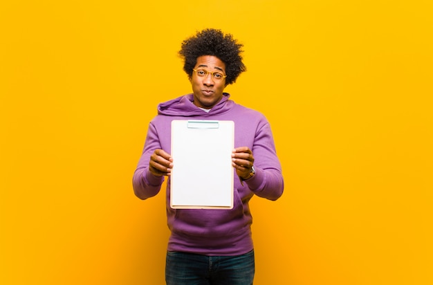 Young african american man  against orange background