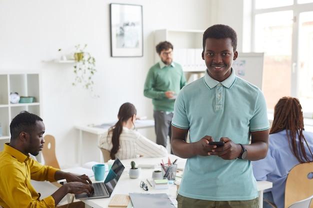 Молодой афро-американский мужчина и улыбается с многоэтнической деловой командой