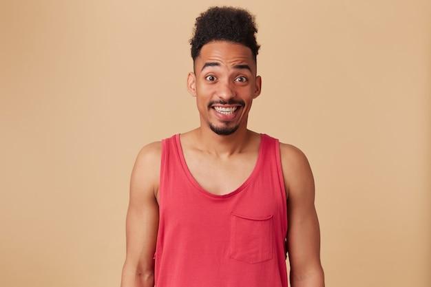 Giovane uomo afroamericano, ragazzo barbuto con acconciatura afro. indossare canottiera rossa. sorridere confuso e incerto. imbarazzato, isolato sul muro beige pastello
