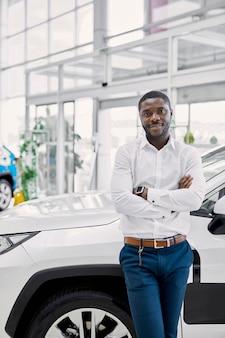 若いアフリカ系アメリカ人の男性がディーラーで自動車を見に来ました
