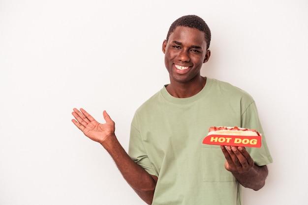 手のひらにコピースペースを示し、腰に別の手を保持している白い背景で隔離のホットドッグを食べる若いアフリカ系アメリカ人の男。