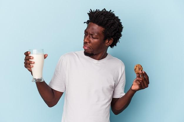 초콜릿 칩 쿠키를 먹고 파란색으로 우유를 마시는 젊은 아프리카계 미국인 남자