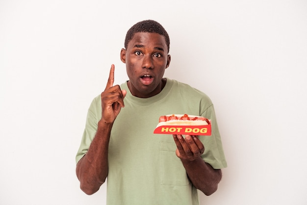 Young african american man eating a hot dog isolated on white background having an idea, inspiration concept.