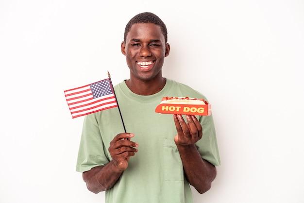 ホットドッグを食べて、白い背景で隔離のアメリカの国旗を保持している若いアフリカ系アメリカ人の男