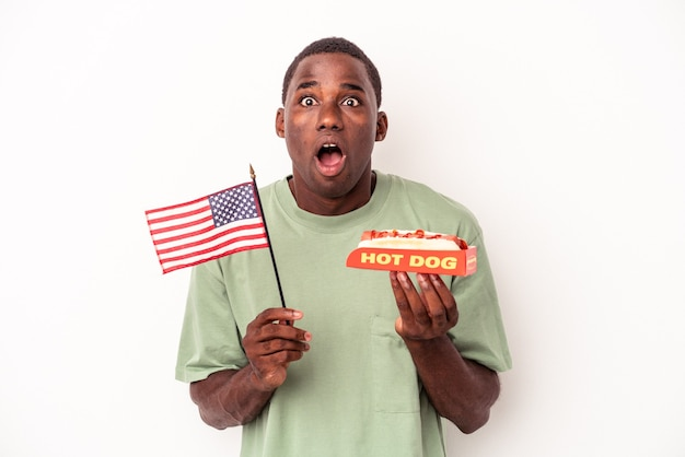 Young african american man eating hot dogs and holding american flag isolated on white background
