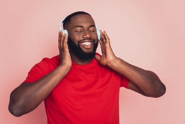 Young african american man enjoy music headset over pink background