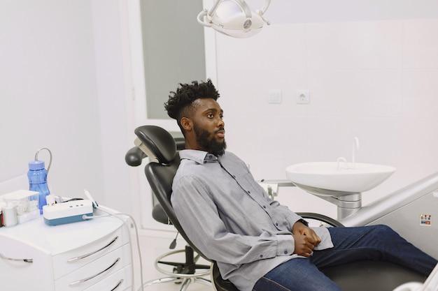 Молодой афро-американский мужчина. парень посещает кабинет стоматолога для профилактики ротовой полости. мужчина и семейный врач во время осмотра зубов.