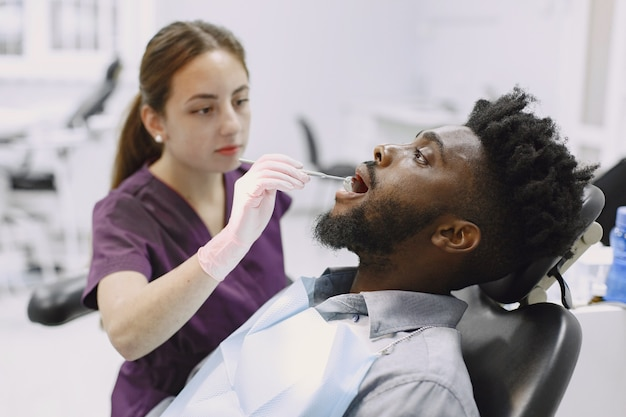 若いアフリカ系アメリカ人の男。口腔予防のために歯科医院を訪れる男。歯の健康診断中の男性と女性の医師。