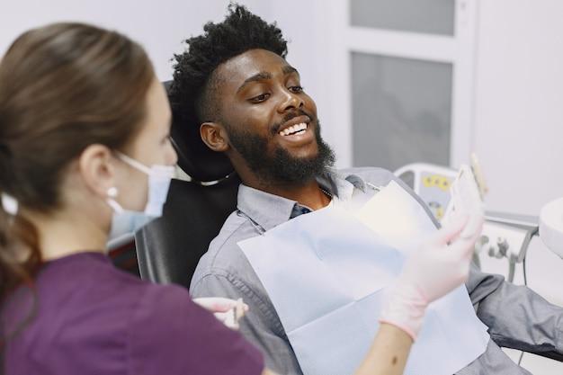 젊은 아프리카 계 미국인 남자. 구강 예방을 위해 치과 의사의 사무실을 방문하는 남자. 검진 치아 동안 남자와 famale 의사.