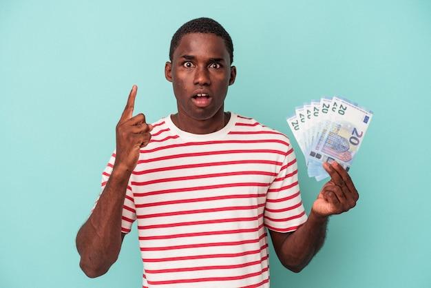 파란색 배경에 격리된 지폐를 들고 있는 젊은 아프리카계 미국인 남자는 훌륭한 아이디어, 창의성 개념을 가지고 있습니다.